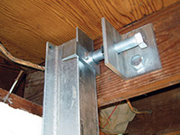Securing the i-beam system to the top of the floor joist in a foundation wall repair in Terrebonne.