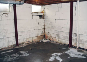 A failed, rusty i-beam foundation wall system installed in Chambly.